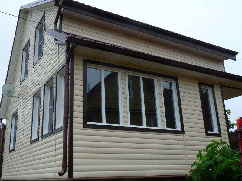 Фасад частного дома, облицованный сайдингом под бревно