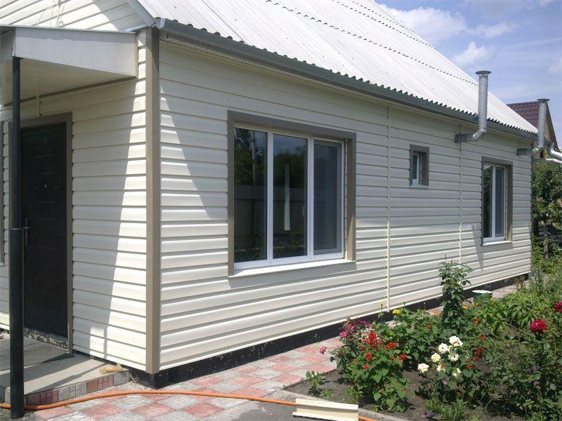 Фасад дома, обшитый белым металлическим сайдингом