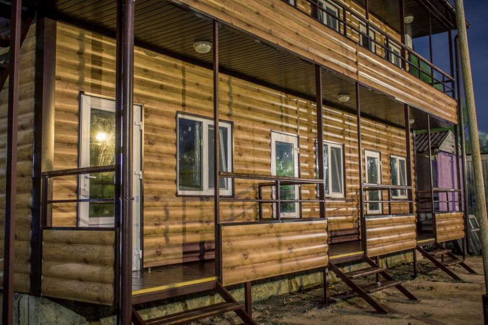 Двухэтажный дом с верандами, обшитый металлическим сайдингом с имитацией блок хауса