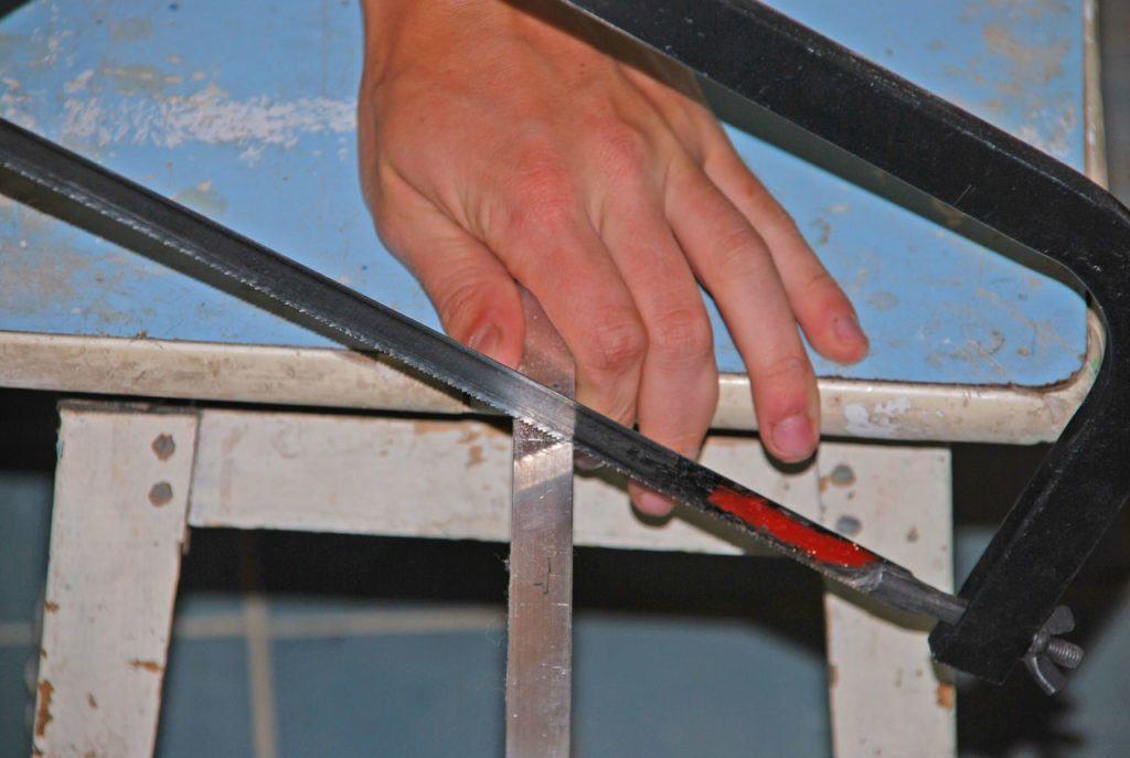 На фотографии представлен процесс распила металла с помощью ножовки по металлу, процесс довольно долгий и трудоёмкий