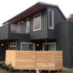 Обшивка фасада и балкона двухэтажного дома вертикальными панелями