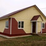 Двухцветный фасад не приемлет дополнительных цветовых пятен, поэтому кровля подобрана в тон